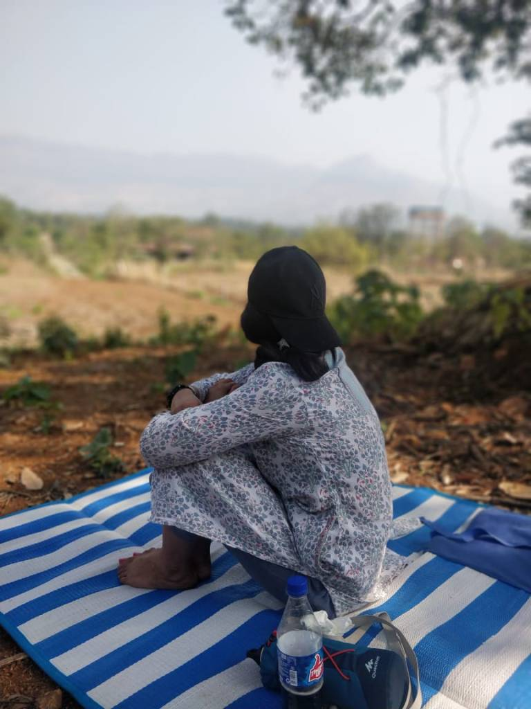 Woman sitting on a mat and looking at the hills